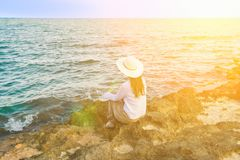 Young Beautiful Woman in Boho Clothes Long Hair Sunhat Sitting on Rocks at Shore Looking at Turquoise Sea Horizon. Golden Sun Flare. Meditation Tranquility Stock Photo