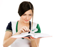 Young beautiful woman with a book. Young beautiful woman reading a book through magnifying glass, white background Stock Photo