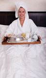 Young beautiful woman with breakfast in bed Stock Photography