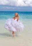Young beautiful woman in a bride dress standing at sea edge Royalty Free Stock Images