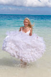 Young beautiful woman in a bride dress standing at sea edge Stock Photo