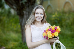 Young beautiful woman with a bright bouquet of Royalty Free Stock Images
