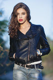 Young beautiful woman with bright trendy makeup wavy hairstyle in black leather jacket  and blue jeans strolling in the park Stock Image
