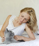 Young beautiful woman with british cat on the bed Royalty Free Stock Photos