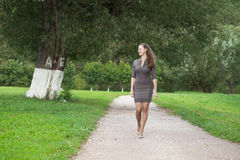 Young beautiful woman in brown dress walks in the summer park Stock Photos