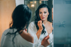Young beautiful woman brunette in the bathroom, and white bathrobe making make-up near mirror. Royalty Free Stock Photo