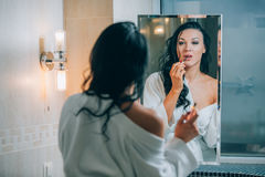 Young beautiful woman brunette in the bathroom, and white bathrobe making make-up near mirror. Stock Photo