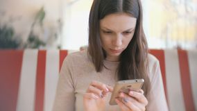 Young beautiful woman brunette browsing internet in her mobile phone in cafe and waiting her friends.  stock footage