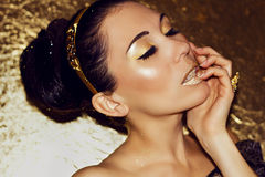Young beautiful woman brunette with retro hairstyle, hoop. Gold make-up. Stock Images