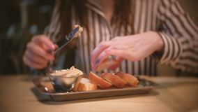 Young beautiful woman brunette smears pate on a piece of bread in cafe. Close-up woman`s hands with knife. Young beautiful woman brunette smears pate on a piece stock video footage