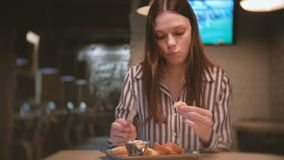 Young beautiful woman brunette smears pate on a piece of bread in cafe with knife. And she eats sandwich. Young beautiful woman brunette smears pate on a piece stock video footage