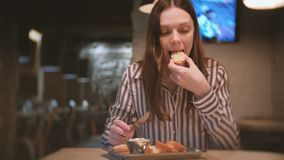Young beautiful woman brunette smears pate on a piece of bread in cafe with knife. And she eats sandwich. Young beautiful woman brunette smears pate on a piece stock video