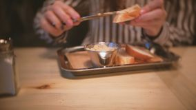 Young beautiful woman brunette smears pate on a piece of bread. Close-up woman`s hands with knife. Young beautiful woman brunette smears pate on a piece of stock video