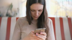 Young beautiful woman brunette typing and sending message in her mobile phone in cafe and waiting her friends. Young beautiful woman brunette typing and sending stock footage