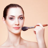 Young beautiful woman with brush for make-u Stock Photo