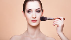 Young beautiful woman with brush for make-u Royalty Free Stock Photography