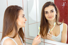 Young beautiful woman brushing teeth in front of the mirror. In a bathroom royalty free stock photography