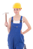 Young beautiful woman builder in blue coveralls with hammer isol Royalty Free Stock Photos