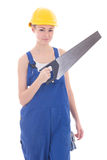 Young beautiful woman builder in blue coveralls with manual saw Royalty Free Stock Image