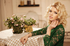 Young beautiful woman in a cafe. Modern trendy blondy girl in th Royalty Free Stock Image