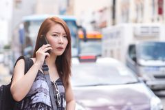 Young beautiful woman calling public taxi by phone royalty free stock photos