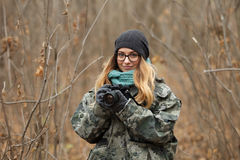 Young beautiful woman in camouflage outfit discovering nature in the forest with photo camera. Travel photography lifestyle concep Stock Photos