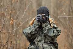 Young beautiful woman in camouflage outfit discovering nature in the forest with photo camera. Travel photography lifestyle concep Stock Images