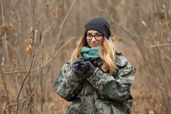 Young beautiful woman in camouflage outfit discovering nature in the forest with photo camera. Travel photography lifestyle concep Royalty Free Stock Images