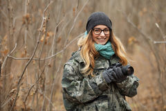 Young beautiful woman in camouflage outfit discovering nature in the forest with photo camera. Travel photography lifestyle concep Royalty Free Stock Photos