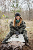 Young beautiful woman in camouflage outfit sitting on forest log discovering nature in the forest with compass and map. Travel lif Stock Photo
