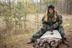 Young beautiful woman in camouflage outfit sitting on forest log discovering nature in the forest with compass and map. Travel lif Stock Photos