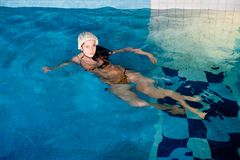 Attractive girl with cap in swimming pool Royalty Free Stock Image