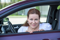 Young beautiful woman in car looking at opened window Stock Photography