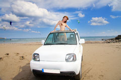 Young beautiful woman in the car on seacoast. Royalty Free Stock Images