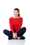 Young beautiful woman in casual clothes. Sitting on floor, isolated on white Royalty Free Stock Images