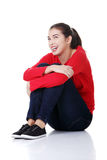 Young beautiful woman in casual clothes. Sitting on floor, isolated on white Stock Photo