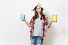 Young beautiful woman in casual clothes and newspaper hat holding paint tin cans isolated on white background. Instruments, accessories, tools for renovation royalty free stock image