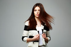 Young beautiful woman in casual clothes. Studio shot of a young beautiful woman in casual clothes on gray background Stock Photography