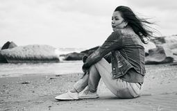 Young beautiful woman sitting on on the stone beach Stock Image