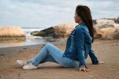 Young beautiful woman sitting on on the stone beach Stock Images