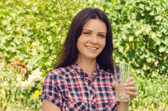 Young beautiful woman in casual shirt holds a glass of water and Royalty Free Stock Photo