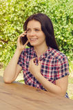 Young beautiful woman in casual shirt smiling and  talking on ph Stock Photos