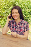 Young beautiful woman in casual shirt smiling and  talking on ph Royalty Free Stock Photography