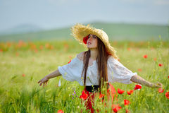 Young beautiful woman on cereal field with poppies in summer Stock Photos