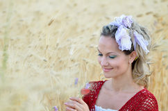 Young beautiful woman on cereal field in summer. Young smiling woman on golden cereal field in summer Stock Photos