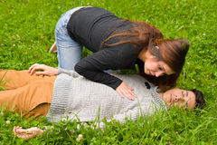 Young beautiful woman checking a handsome young man if he still breathing, cardiopulmonary resuscitation concept, in a Royalty Free Stock Images