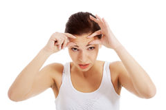 Young beautiful woman is checking her wrinkles on forehead. Royalty Free Stock Images