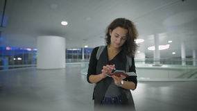 A young beautiful woman is checking new in her phone before the trip. A beautiful lady is waitinf for her trip at the airport stock footage