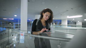 A young beautiful woman is checking news in her phone and smiling stock footage