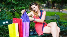 Young beautiful woman checking the shopping bags. Stock Photos